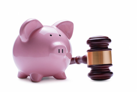 repayment: Porcelain pink piggy bank next to a wooden judge gavel, concept of savings, economic litigations and auctions, close-up with shadow on white
