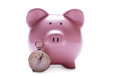 Porcelain pink piggy bank next to a vintage compass, concept of savings and guidance, close-up with shadow on white Stock Photo