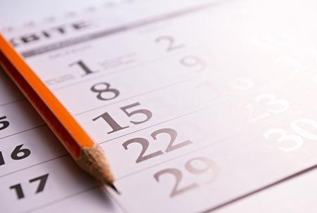 calendario: Primer plano de un l�piz afilado en la p�gina de un calendario, con el fin de marcar los d�as con eventos Foto de archivo