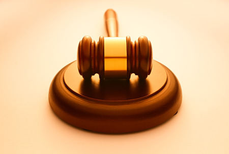 judgements: Wooden gavel with a brass band resting on a plinth used by a judge or auctioneer and conceptual of justice and judgements with backlit highlight and copyspace