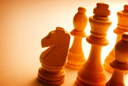 pawn king: Close-up of wooden vintage chess pieces as knight, pawn, king and bishop Stock Photo
