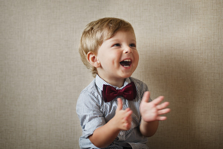 aplaudiendo: Niño pequeño hermoso que lleva una pajarita marrón con estilo riendo y aplaudiendo con sus manos sobre una pared gris con viñetas