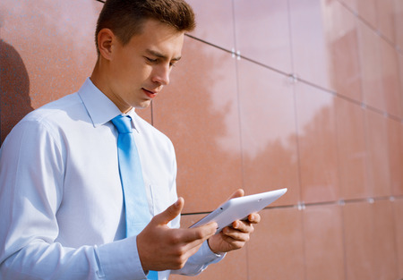 Serious Businessman Looking Down at Tablet Computer and Leaning Against Wall