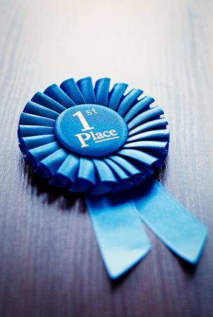 primer lugar: En primer lugar los ganadores roseta o insignia en la cinta plisada azul con texto central que se adjudicarán como premio en un concurso, la raza, o el deporte en un ángulo oblicuo en gris con copyspace