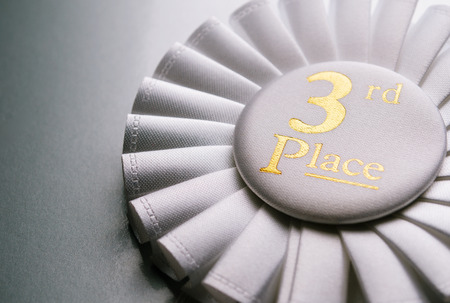 high quality: 3rd place white winners rosette with gold text made from pleated ribbon, close up view Stock Photo