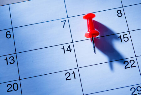 marked: Red pin marking the 15th on a calendar as a reminder of an important event, close up low angle view