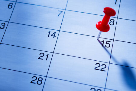 important reminder: Red pin marking the 15th on a calendar as a reminder of an important event, close up low angle view