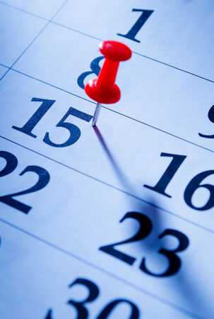 event calendar: Red pin marking the 15th on a calendar as a reminder of an important event, close up low angle view