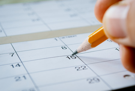organizer: Person marking the date of the 15th with a pencil on a blank calendar with date squares as a reminder of an important day or to schedule a meeting or event