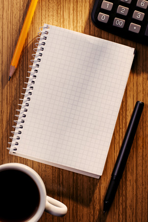 Notebook and Calculator on Desk with Cup of Coffee as seen from Above with Various Writing Instruments photo
