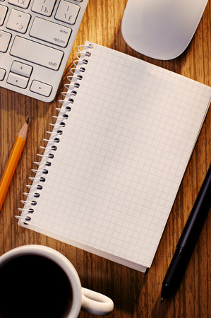 Open notebook with blank white lined pages with a cup of black coffee alongside a computer keyboard on a wooden desk, overhead view photo