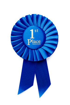 Circular pleated blue ribbon winners rosette with central text - 1st Place - in gold, isolated on white