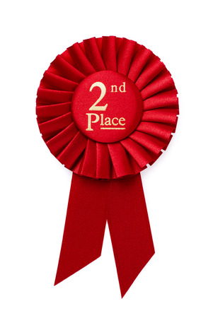 Red 2nd place ribbon rosette with gold central text in a pleated surround isolated on white