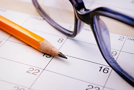 Calendar, pencil and glasses for planning important things and to set a date.