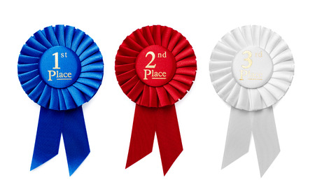 1st, 2nd and 3rd Place pleated ribbon rosettes or badges in blue, red and white respectively with central text isolated in a row on a white background, overhead view Stockfoto