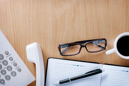 eye wear: Telefonista Stuffs - desgaste del ojo, cuaderno y pluma y una taza de caf� en la mesa de madera en la Oficina. Foto de archivo