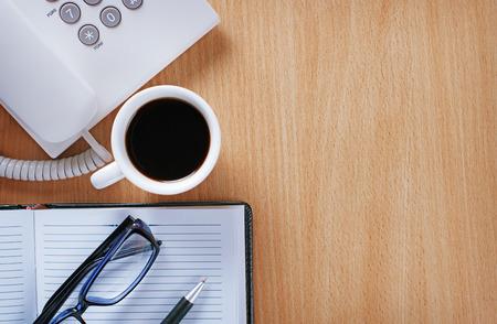 eye wear: Cierre de Stuffs sobre tabla de madera de un hombre de negocios con una taza de caf� puro Negro, Notas y pluma, desgaste del ojo y tel�fono en la Oficina Foto de archivo