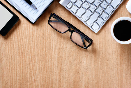 Close up Reading Eye Glasses on Businessman Wooden Table with Other Stuffs - Coffee, Keyboard, Notebook, Pen and Phone.
