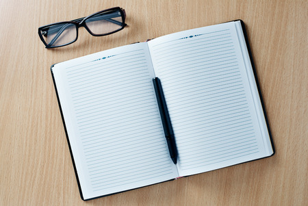 Open diary or office journal with a double page lined blank spread for your text with a ballpoint pen and glasses on a wooden desk, overhead view photo