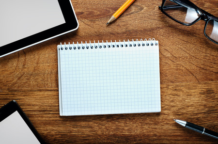 Close up Blank Graphing Notebook on Wooden Desk with Copy Space for Text, Surrounded with Gadgets, Pen, Pencil and Eyeglasses. photo