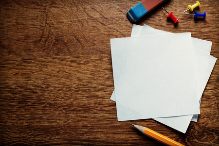 reminders: Stack of small square blank white memo pages with a pencil for jotting notes and reminders and thumbtacks to attach to a notice board, overhead view on a wooden desk