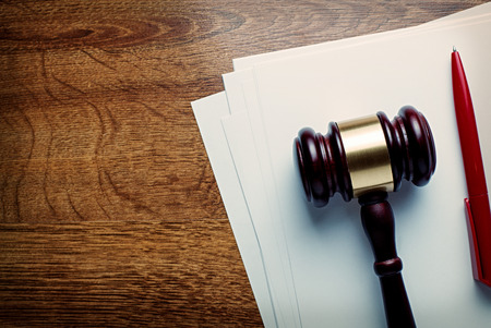 auctioneer: Wooden judges or auctioneers gavel and blank white paper lying on a wooden desk with a ballpoint pen in a concept of judgements or auction knock down, with copyspace Stock Photo