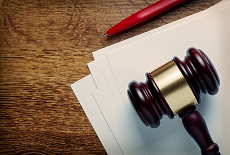 sentencing: Wooden judges or auctioneers gavel and blank white paper lying on a wooden desk with a ballpoint pen in a concept of judgements or auction knock down, with copyspace Stock Photo