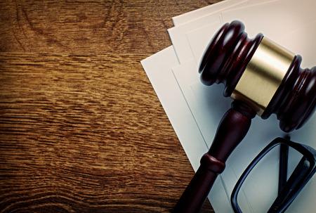 Holz-Hammer mit einer Blaskapelle und Gläser auf Briefpapier konzeptionelle eines Urteils in Recht, Gerechtigkeit oder Versteigerer Hammer, Ansicht von oben auf einem hölzernen Schreibtisch mit Exemplar