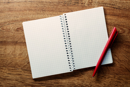 Open blank white square ruled spiral bound notebook with copyspace and a red ballpoint pen lying on a wooden desk, view from above photo