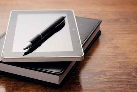 emphasizing: Close up Electronic Tablet Device on Notebook Resting on Wooden Table. Emphasizing Learning Concept. Stock Photo