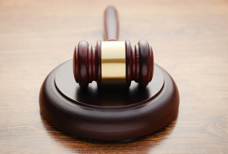 pronounce: Judges wooden gavel in a courtroom lying on its plinth ready to pronounce judgment and sentencing Stock Photo