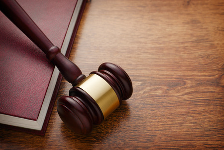 emphasizing: Close up Brown Wooden Gavel and Maroon Book on Top of Wooden Table, Emphasizing Legal or Law Concept