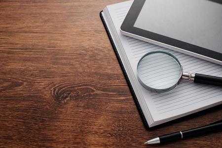 lupa: Cierre de Tablet Gadget y lupa sobre Top of Open Notas, Descansar en mesa de madera en el borde derecho, con espacio de copia en el lado izquierdo para los Textos.