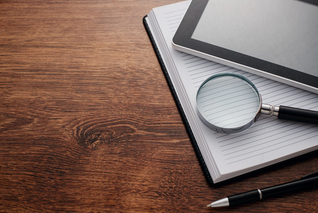 magnifying glass: Close up Tablet Gadget and Magnifying Glass on Top of Open Notes, Resting on Wooden Table at the Right Edge, with Copy Space on Left Side for Texts. Stock Photo