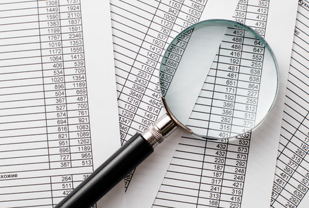 emphasizing: Close up Single Magnifying Glass with Black Handle on Top of Business Reports with Printed Numbers. Emphasizing Business Concept. Stock Photo