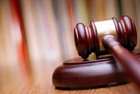 the litigation: Close up Shiny Wooden Law Gavel in Dark Brown Color, on Top of Wooden Table at the Office. Stock Photo