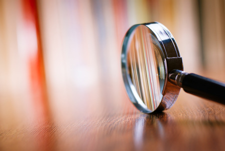 Close up Single Magnifying Glass with Black Handle, Leaning on the Wooden Table at the Office.