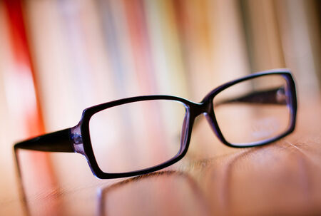 unisex: Close up Unisex Eyeglasses with Black Frame on Top of Wooden Table at the Office.
