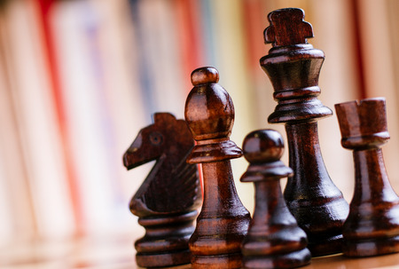 Close up Glossy Black Wooden Chess Pieces- King, Bishop, Knight, Rock and Pawn, Standing on Chess Board.