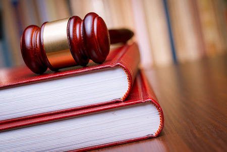 Judges wooden gavel resting on a large red law book on a table in court in a conceptual image of justice and law enforcement Stock Photo