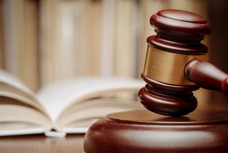 definitive: Martillo de madera de descanso en su extremo sobre una mesa de madera delante de un libro de ley abierto conceptual de un juez, tribunal y juicios Foto de archivo