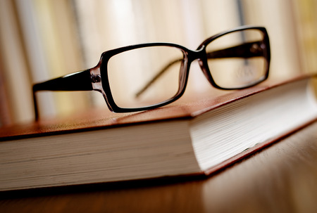 books on a wooden surface: Unisex Eyeglasses on Top of Thick Book Resting on Wooden Table at the Office. Emphasizing Learning or Knowledge Concept.