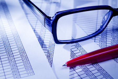 consolidate: Close up Conceptual Unisex Eyeglasses and Red Pen on Top of Business Sales Documents.