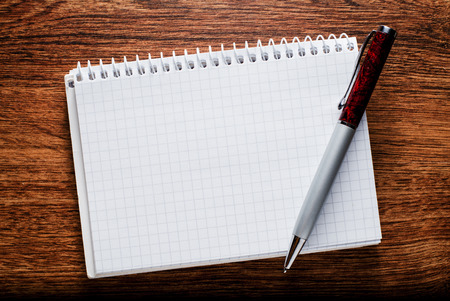 graphing: Close up Conceptual White Blank Graphing Notebook and Pen with Copy Space for Text. Resting on Brown Wooden Table.