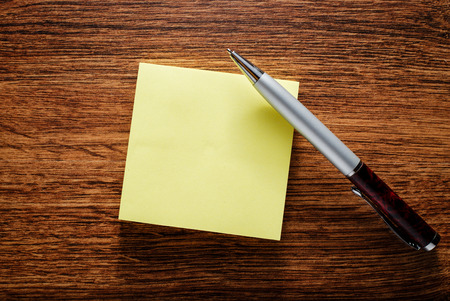 blank area: Close up Clean Blank Yellow Notepad for Text Area and Ball Point Pen on Top of Wooden Table Stock Photo