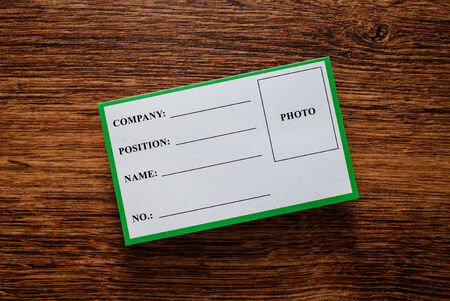 insider information: Blank company identification tag with space for a photograph lying on a wooden table, overhead view