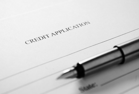 business credit application: Blank credit application form and fountain pen viewed high angle with focus to the header - Credit Application - in a conceptual image
