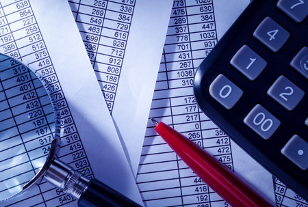 emphasizing: Close up Black Calculator and Red Pen on Top of Paper Reports with Numerical Prints. Emphasizing Business Sales Concept. Stock Photo