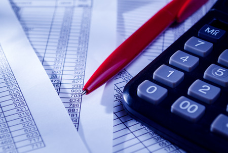 Close up Black Calculator and Red Pen on Top of Paper Reports with Numerical Prints. Emphasizing Business Sales Concept. Banque d'images