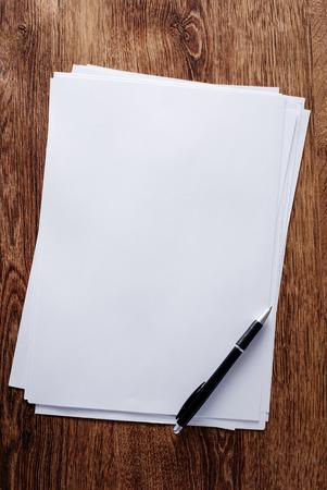 hoja en blanco: Cierre de Clean Bonos Papeles y pluma, con espacio de copia para los Textos, en la cima de la tabla de Brown de madera.